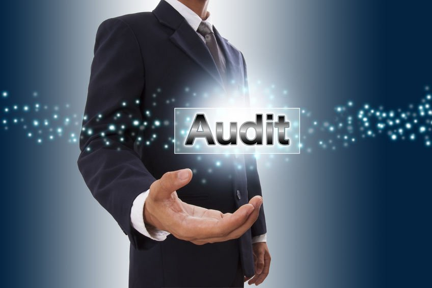 The word Audit highlighted in a businessman's hand